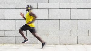Fit black man running so fast his image starts to blur