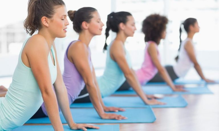 women doing yoga in a studio laying on their stomachs pushing up