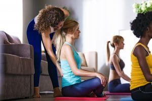 Shot of pretty yoga instructor helping her student in a yoga session at home.