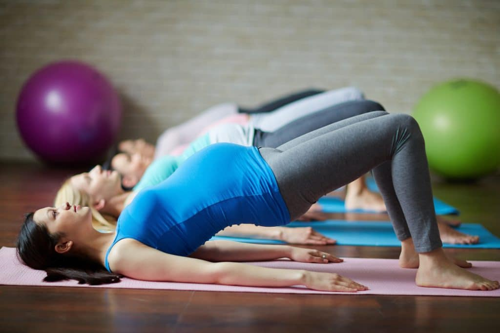 Group of pregnant females exercising on mats in gym