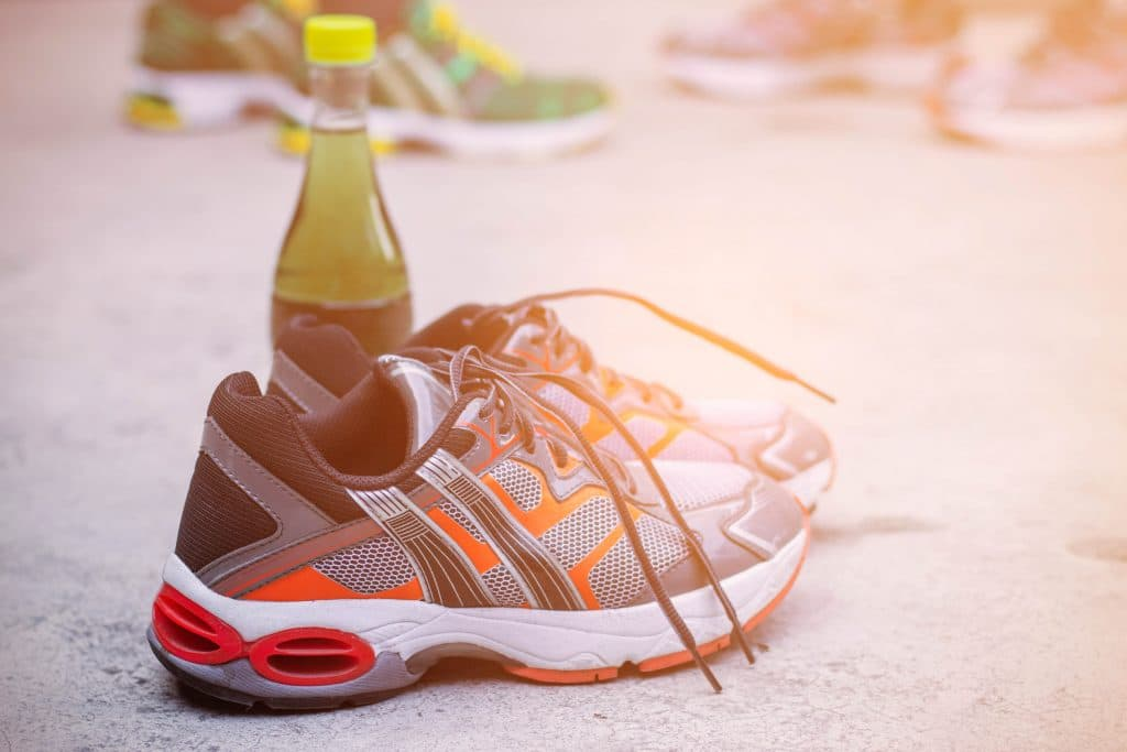 Running shoes and water bottles to health on floor.