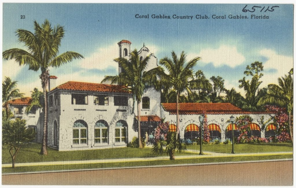 postcard image of a building with trees all around it