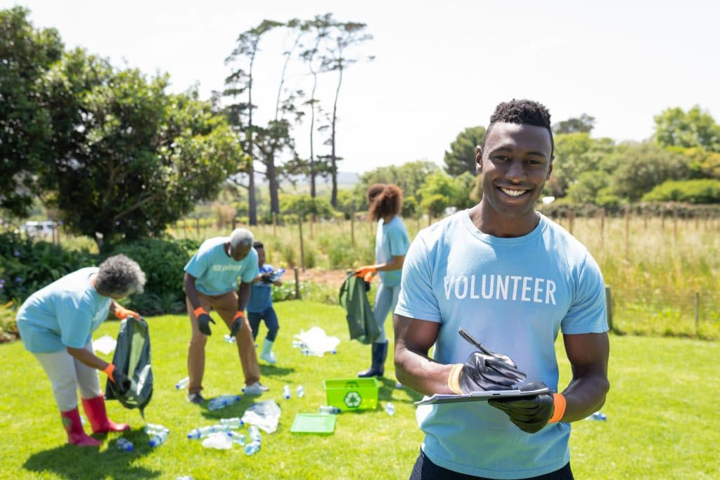 Portrait of a smiling young African American man standing in a field wearing wearing a t shirt with volunteer written on it and gloves, writing on a clipboard and smiling to camera, while a diverse group of volunteers collect rubbish and recycling in the background