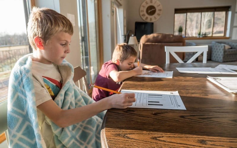 children being home schooled sitting at a table