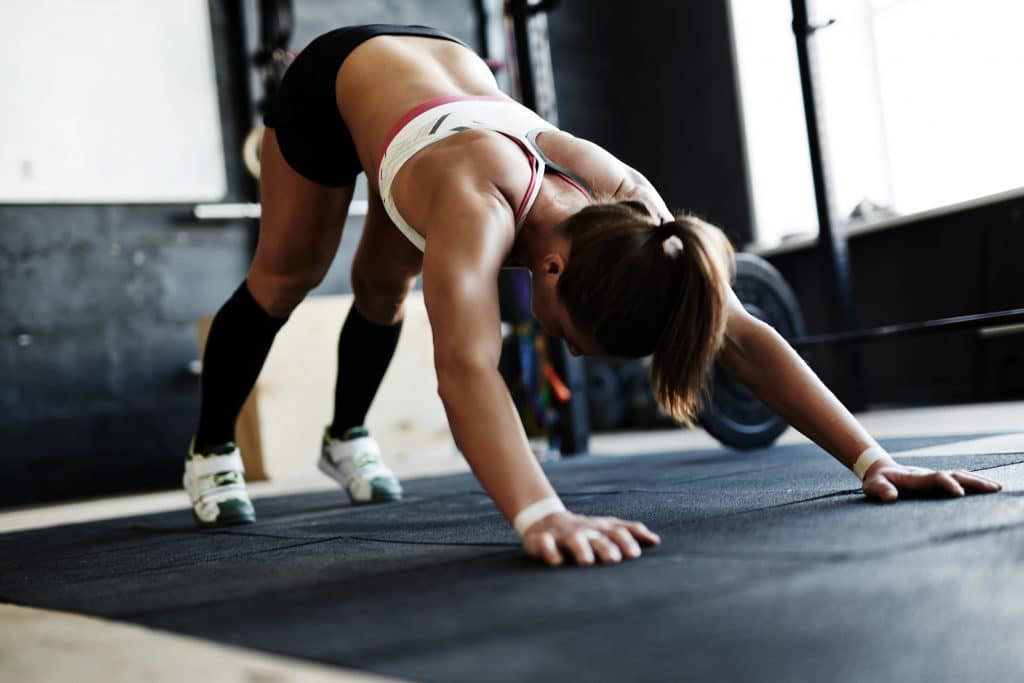 Active young woman doing push-ups on floor of gym
