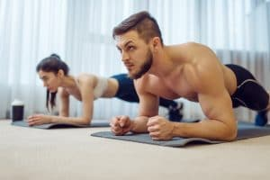 Morning fitness workout of family couple at home. Active man and woman in sportswear doing push up exercise in their house, healthy lifestyle, physical culture