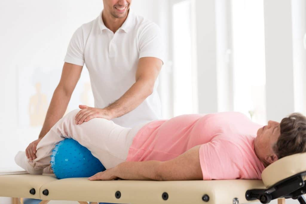 Can I Get Adjusted if I Have Osteoporosis?Smiling therapist massaging an old woman with osteoporosis using a blue ball