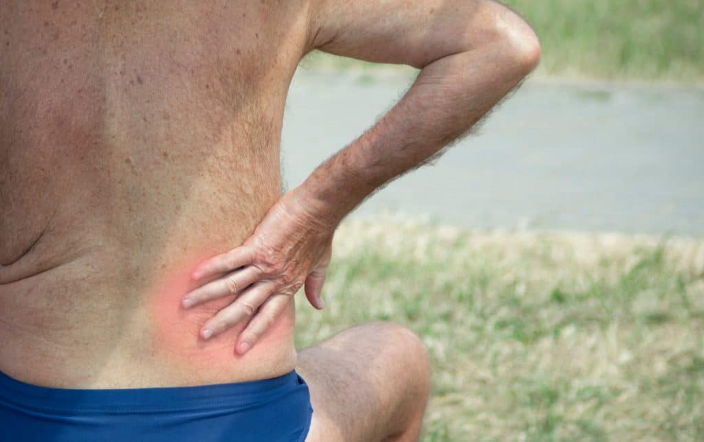 Elderly person holding hand for an inflamed place on the lower back