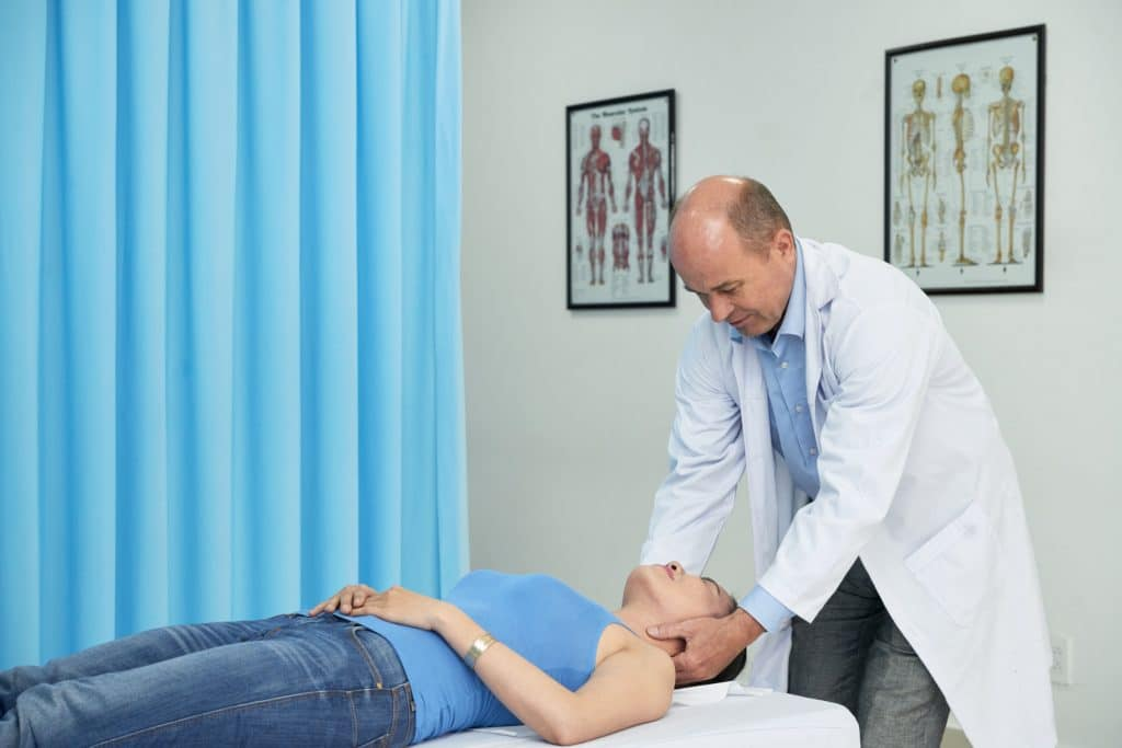 Manual therapist massaging neck of female patient