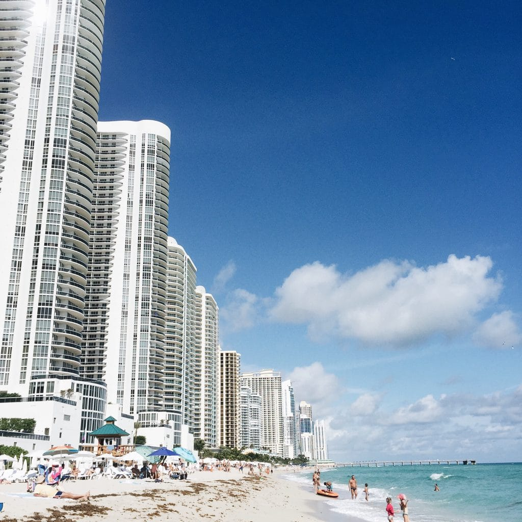 Picture of Miami Beach showing people sunbathing and some of the buildings nearby
