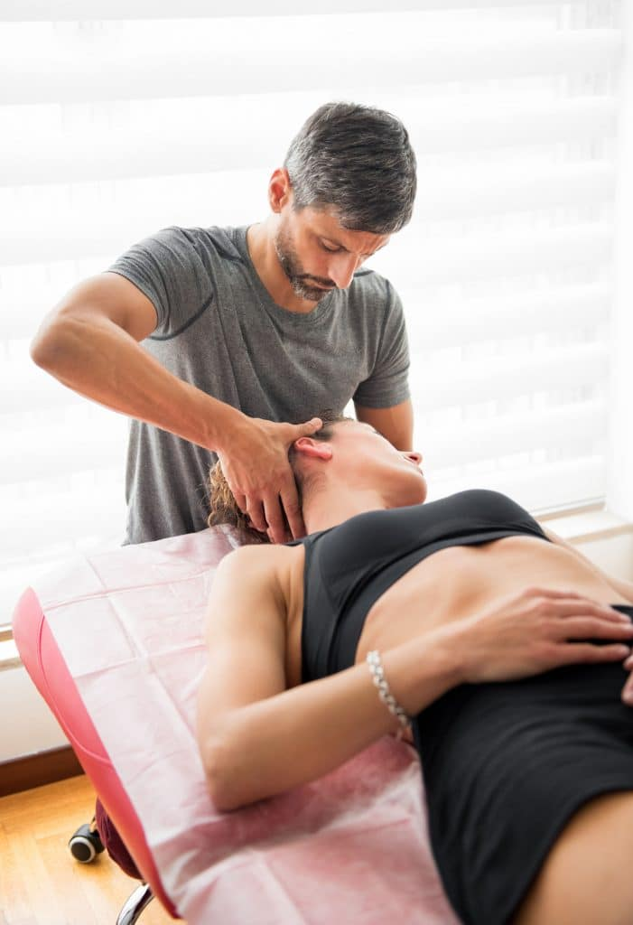 Male osteopath performing cervical trust therapy on the neck of a young female patient in his practice during a consultation in an alternative medicine and healthcare concept