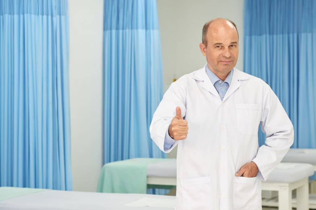 Smiling middle-aged professional chiripractor in labcoat showing thumbs-up