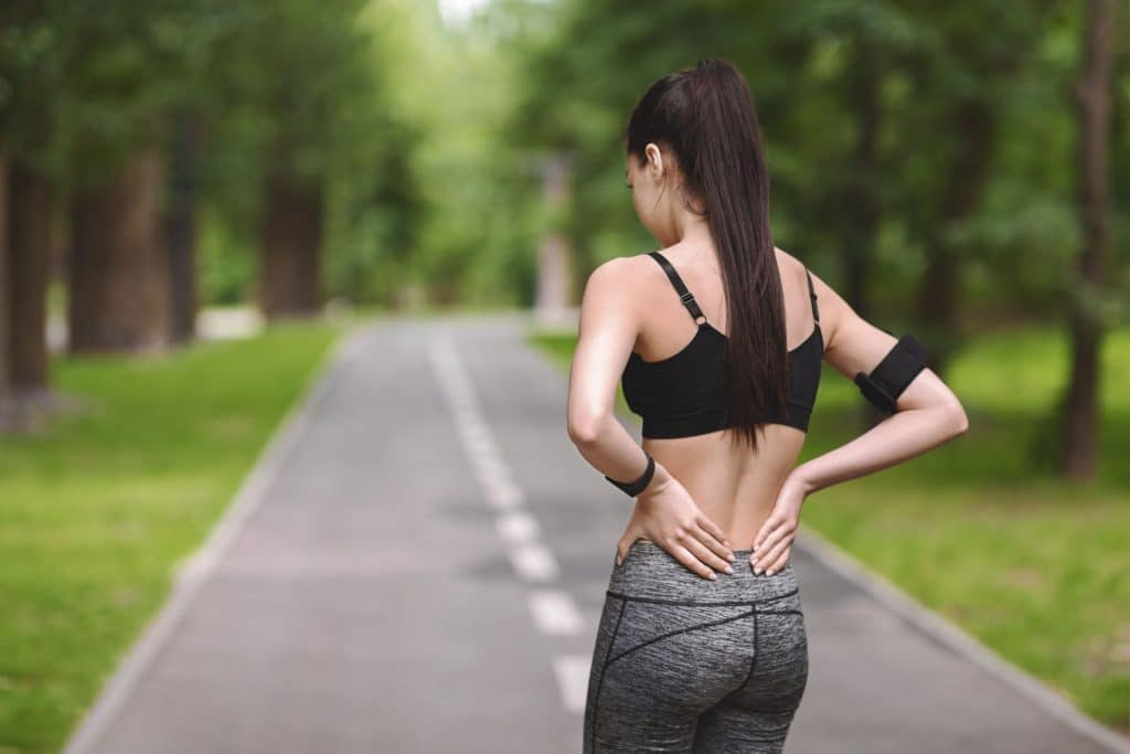 Back Pain. Young fit woman rubbing muscles of her lower back outdoors