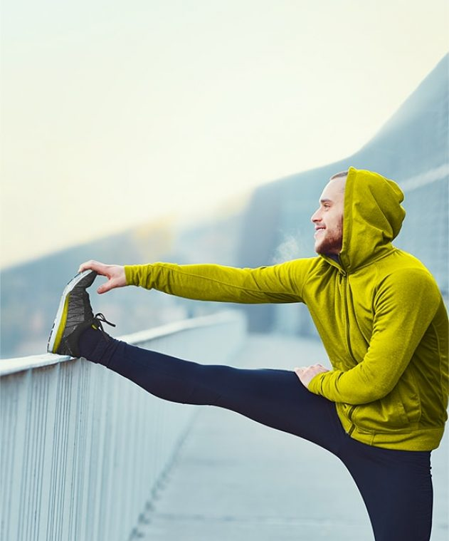 man stretching his leg on a railing while wearing a hoodie